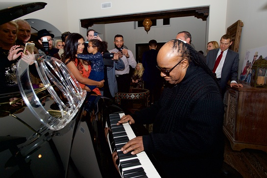 Stevie Wonder brings everyone together around the piano.