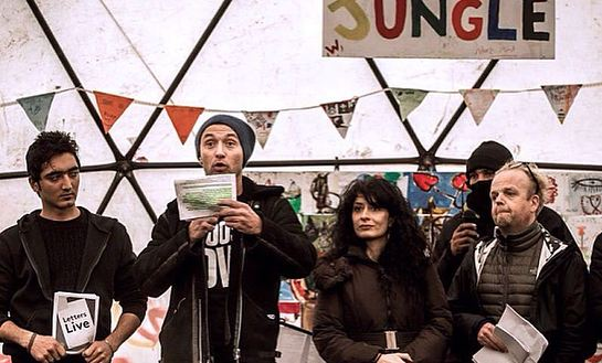 Barbak (a refugee), Jude Law, Shappi Khorsandi and Toby Jones at the Good Chance theatre in the Calais Camp