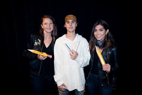 Pencils of Promise executives Leslie Engle Young (L) and Natalie Ebel (R) present Justin Bieber with the first-ever Pencils of Promise Global Ambassador award