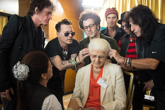 Joe Perry, Johnny Depp, Bruce Witkin, Robert DeLeo, Tommy Henriksen and Alice Cooper of the Hollywood Vampires install an hearing aid on a patient of the Starkey Hearing Foundation