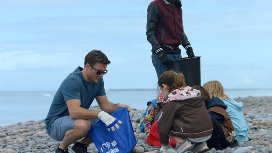 Scott Eastwood with volunterring children at Surfrider beach cleanup