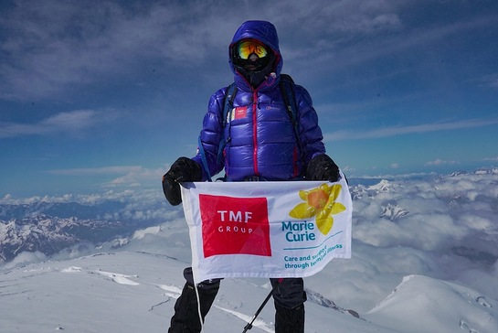 TMF Group brand ambassador Sir Ranulph Fiennes holds Marie Curie banner at the top of Mount Elbrus