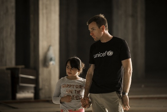 Ewan McGregor walks with Myrna, 10, inside an abandoned mall that her and her family used to live in, Erbil, northern Iraq