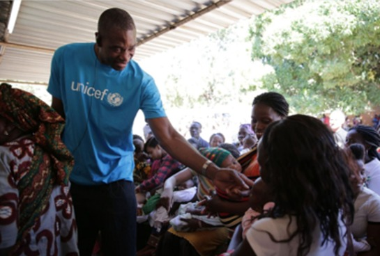 Dikembe Mutumbo greets mothers and babies at a severe acute malnutrition center in Maputo, Mozambique