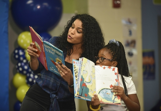 Jordin Sparks reads with a student from Amidon-Bowen Elementary School during Reading Is Fundamental's 50th Anniversary
