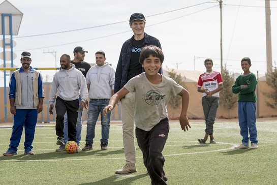 Liam Neeson plays football during a visit to a Makani centre in Za'atari refugee camp in Jordan