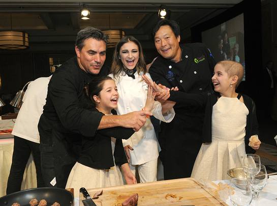 Chef Todd English, singer Daya, and chef Ming Tsai, left to right, with twins Sabrina and Olivia Lorusso, front, celebrate at Family Reach's Cooking Live! charity event