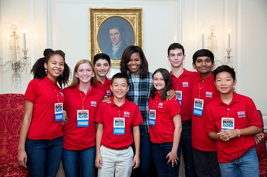 Michelle Obama joins Scholastic News Kid Reporters for a group photo following an interview in the Map Room of the White House