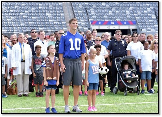 Eli Manning stands with doctors, nurses, team members, patients and families from Hackensack University Medical Center as a part of the Tackle Kids Cancer campaign