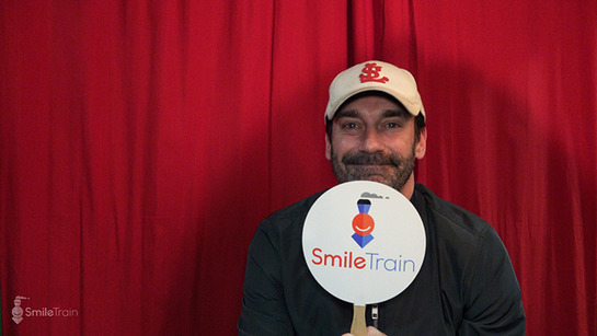Jon Hamm shows off a Smile Train fan backstage at the Eighth Annual Pardcast-a-Thon
