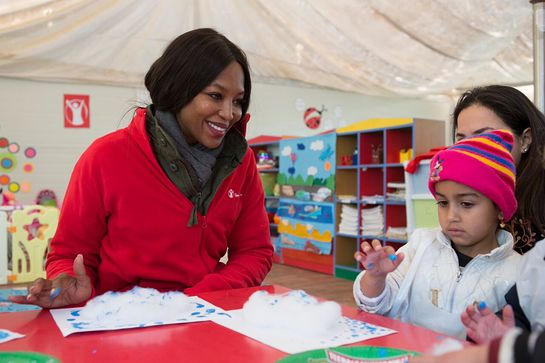Naomi Campbell participates in a finger painting class with 4-year-old Yara at Save the Children's Sunshine Kindergarten
