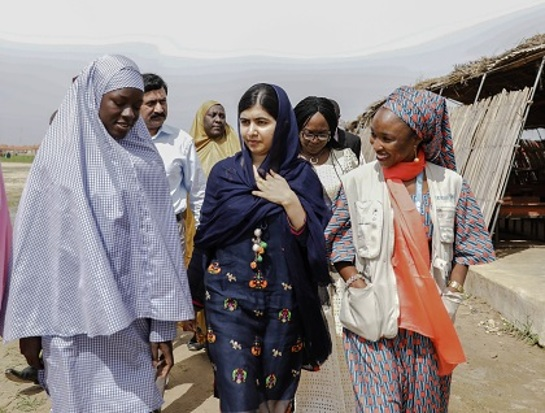 Malala Yousafzai is shown around the school in Bakassi camp by student, Fatima Grema