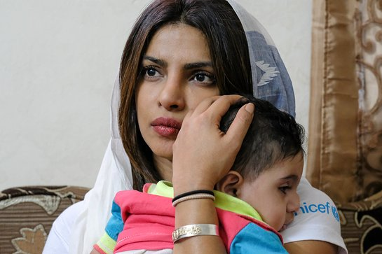 Priyanka Chopra holds 5 year old Suleiman during a visit to his home in Amman, Jordan