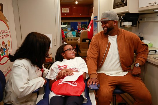 C.C. Sabathia, right, listens as Colgate Bright Smiles, Bright Futures dental coordinator Dr. Dominique Juste, left, shares oral health tips with P.S. 129 student Reina Copeland