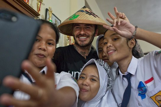 David Beckham poses with students at the SMPN 17 school in Semarang, Indonesia