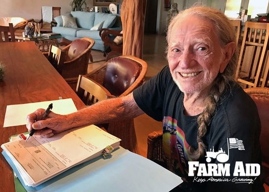Farm Aid President Willie Nelson signs 2018 grant checks from his kitchen table