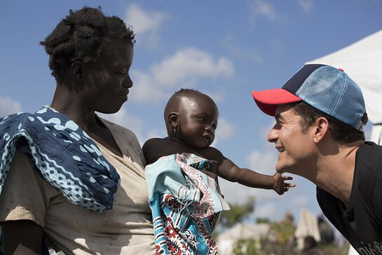 Orlando Bloom visits with Logina Jona, 5 months, and her mother Sonia Paulo Jona in the Mutua Resettlement Site
