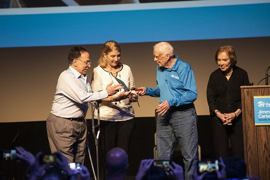 Jimmy Carter and former First Lady Rosalynn Carter passing a ceremonial trowel to Cesarina Fabian and Celso Marranzini