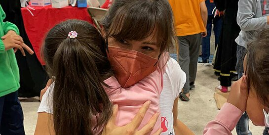 Jennifer Garner receives a hug from a girl at a temporary shelter for Afghan children