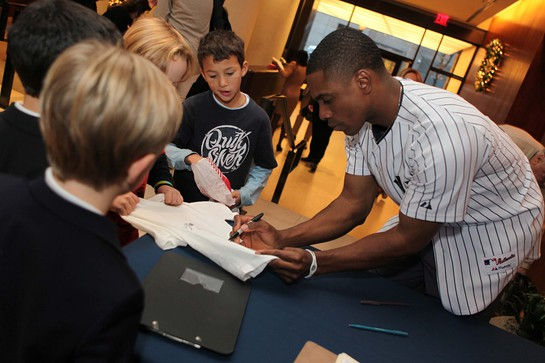 Curtis Granderson signs photos and chats with his young fans.