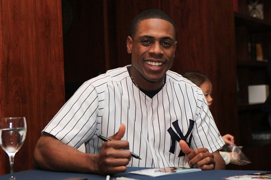 Curtis Granderson poses while signing photos for fans.