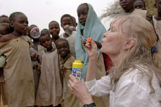 Mia Farrow blows soap bubbles to the delight of children at the Zam Zam camp for people displaced by the conflict in Darfur.