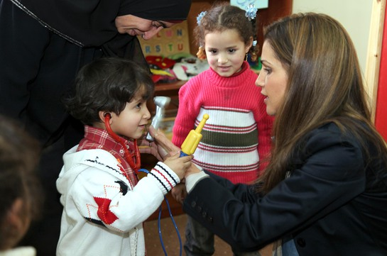 A boy pretends to be a doctor with Queen Rania.