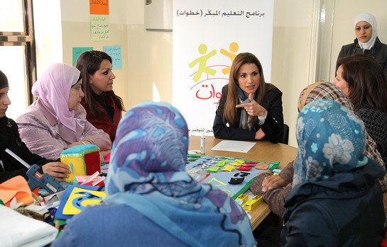 Mothers show Queen Rania some of the learning materials they learned how to make.