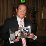 Roger Moore Signs Toy James Bond Cars For Celebrity Charity Auction