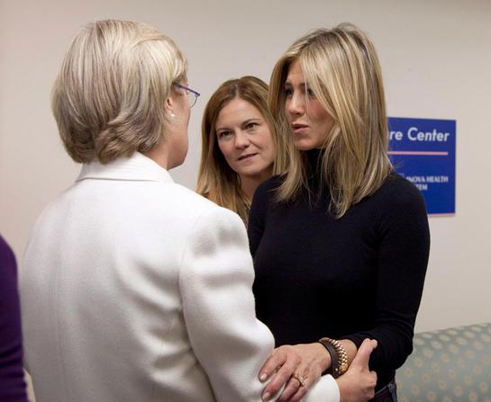Producer Kristin Hahn, center, and actress and producer Jennifer Aniston, talk with a breast cancer survivor at the Inova Breast Care Center (AP Photo/Carolyn Kaster)