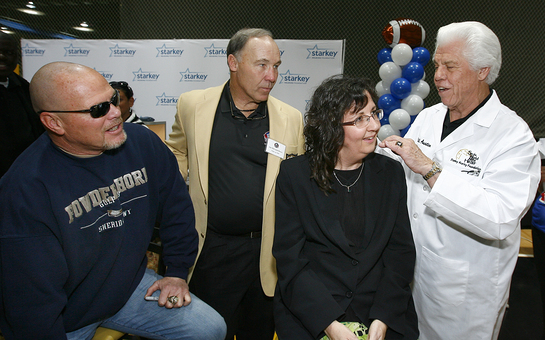 Joe DeLamielleure and Jim McMahon Help Bill Austin Provide Catherine Donaldson With Hearing Aids