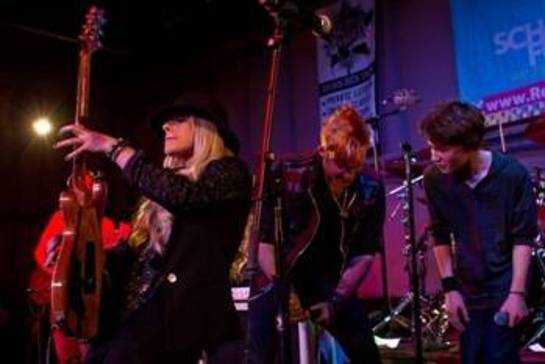 In this photo, Orianthi (left) is shredding while James Durbin (center) rocks out with one of the students.