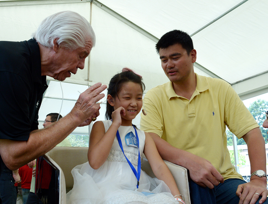 Girl receives the gift of hearing with Bill Austin, Founder, Starkey Hearing Foundation (left) and NBA Legend Yao Ming (right)