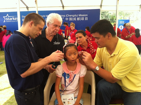 Child is fit by David Shoemaker, CEO, NBA China; Bill and Tani Austin, Co-Founders, Starkey; and NBA Legend Yao Ming.