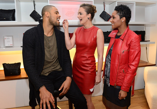 Tyson Chandler getting his cheek swabbed by DKMS Delete Blood Cancer co-founder Katharina Harf and wife, Kimberly, wearing Bally Lips for Life Collection