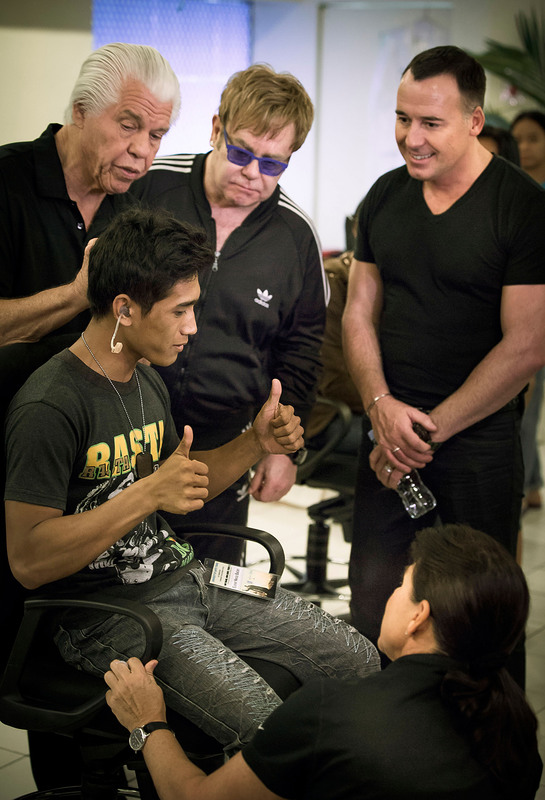 Elton John, David Furnish and Starkey Hearing Foundation founders Bill and Tani Austin help a young man hear during the Foundation's mission in Manila