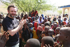 Michael Sheen sings and plays with children next to a rural health centre in Chad supported by UNICEF
