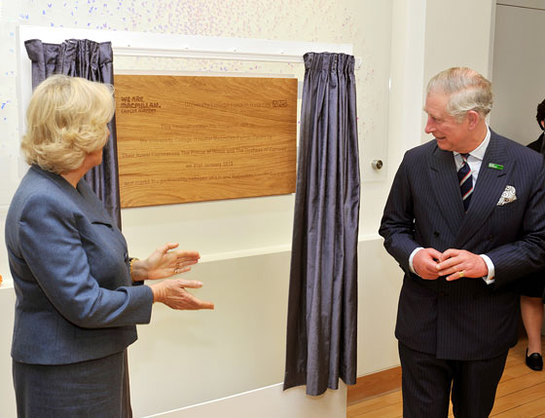 The Prince of Wales and the Duchess of Cornwall admire a wooden plaque unveiled by the Prince, during a tour of the new Macmillan Cancer Support unit
