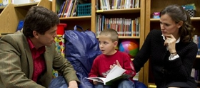 Jennifer Garner and Mark Shriver read with a child participating in Save the Children's early education program