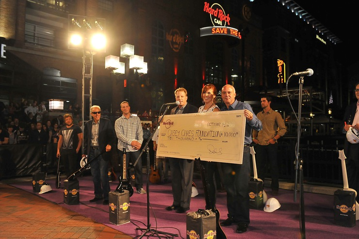 Fred Thimm, Vice President of Hard Rock International, Casey Baynes, Founder of the Casey Cares Foundation, and Hamish Dodds, President and CEO of Hard Rock International present a $10,000 donation to The Casey Cares Foundation