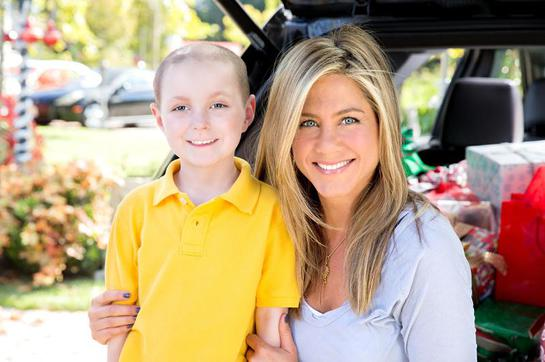 St. Jude Thanks and Giving celebrity supporter Jennifer Aniston smiles alongside St. Jude patient Cash
