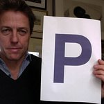 Hugh Grant Holds A Purple P For Charity