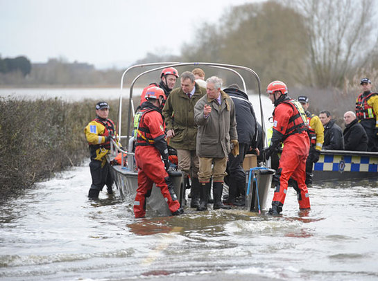 The Prince of Wales steps from a boat after travelling to the flood-hit community of Muchelney