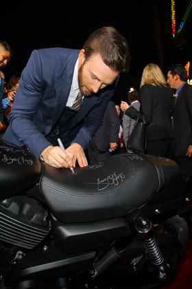 Chris Evans signs a new Harley-Davidson Street 750 at the premiere in Hollywood, CA.