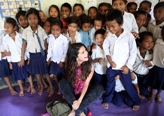 UNICEF Ambassador, Selena Gomez enjoys a sweet moment with a student while the early childhood education class gathers for a group photo at Satbariya Rapti Secondary School