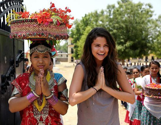 Selena Gomez is greeted by students at Satbariya Rapti Secondary School wearing traditional Nepali clothing