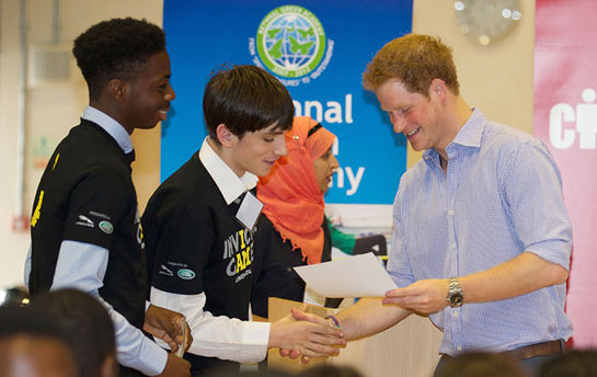 Prince Harry poses for a group photograph during a visit to Bethnal Green Academy