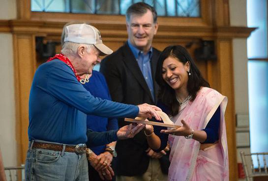 Former President Jimmy Carter passes a symbolic wooden trowel to Habitat for Humanity Nepal representative Sushma Shrestha