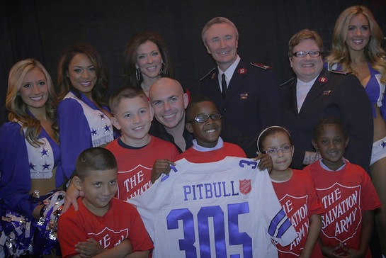 Pitbull was joined by the Dallas Cowboys cheerleaders Friday during his concert in Dallas to announce that he will kickoff The Salvation Army Red Kettle Campaign