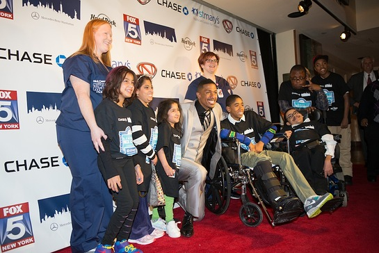 Nick Cannon poses on the red carpet at Hard Rock Cafe in Times Square with children and staff from St. Mary's Children's Hospital